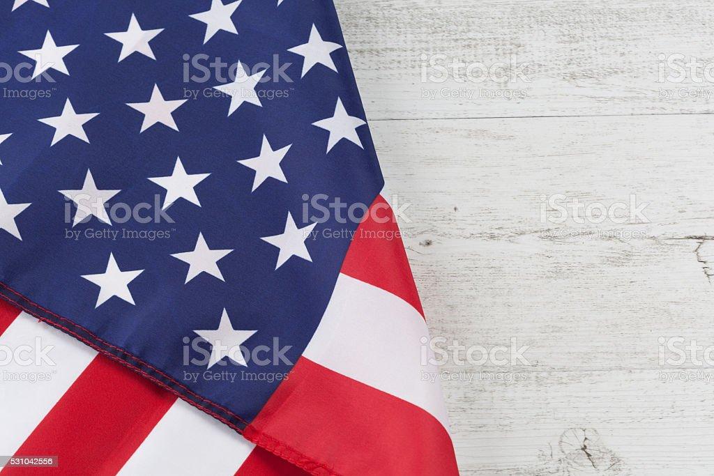 USA flag folds on white rustic wood stock photo