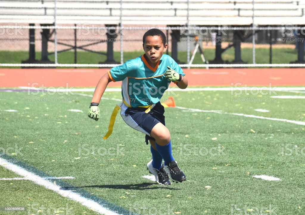 10 year old mixed race boy running in flag football game, summer...