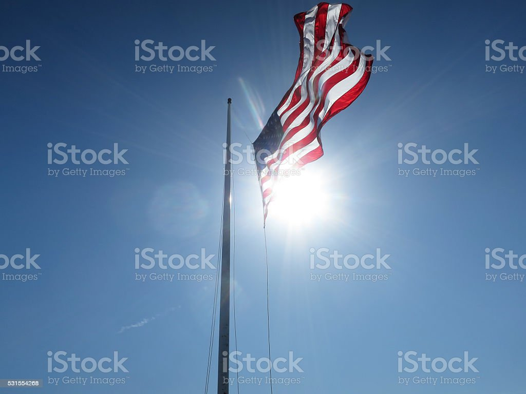 US Flag Half Mast Blue Sky Sun Flare stock photo