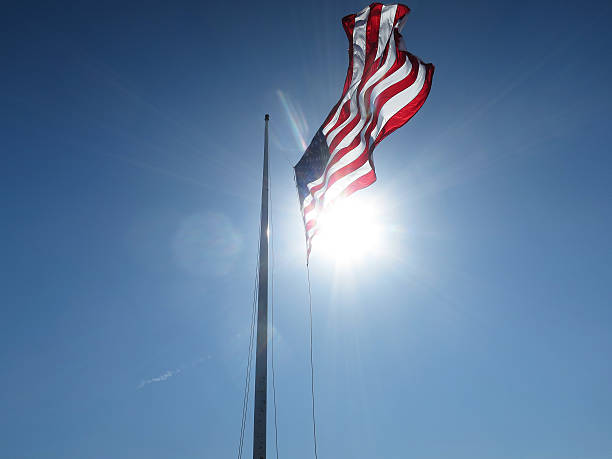 US Flag Half Mast Blue Sky Sun Flare stock photo