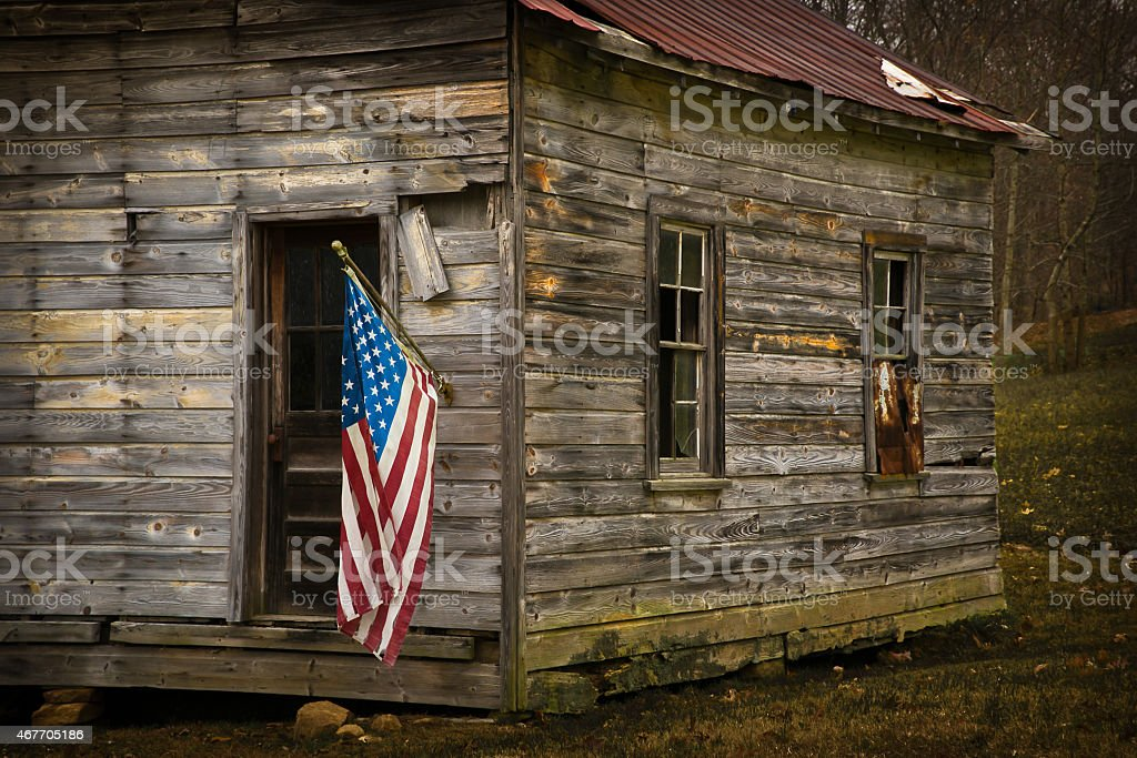 USA Flag Hangs From an Old Cabin Horizontal stock photo
