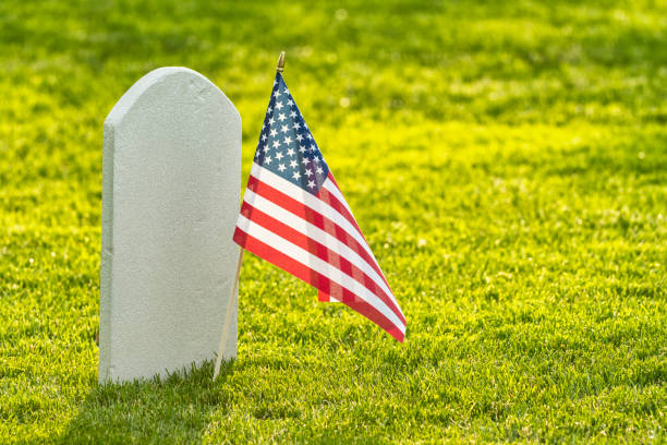 A US flag in front of a lone veteran's tombstone at sunset - Memorial Day stock photo