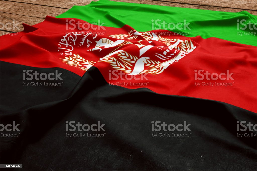 Flag of Afghanistan on a wooden desk background. Silk Afghan flag top view. stock photo