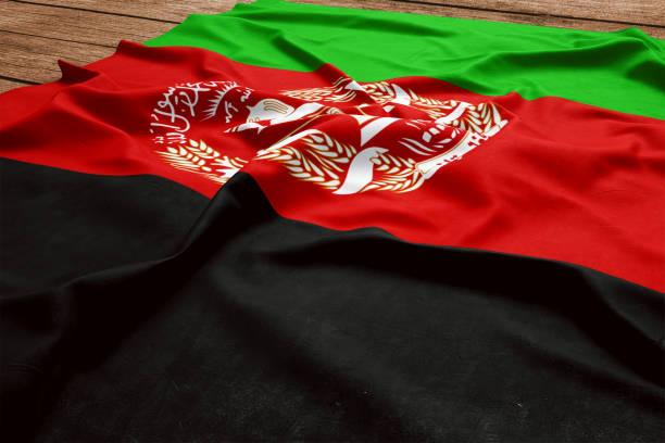 Bandeira do Afeganistão em um fundo de mesa de madeira. Vista superior de seda bandeira afegã. - foto de acervo