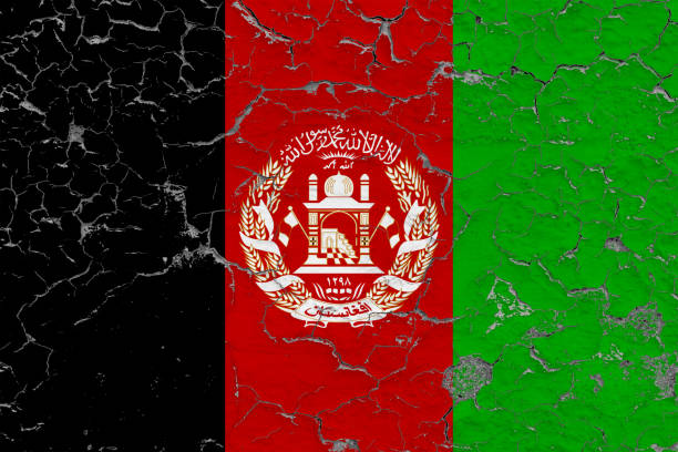 Flag of Afghanistan painted on cracked dirty wall. National pattern on vintage style surface. stock photo