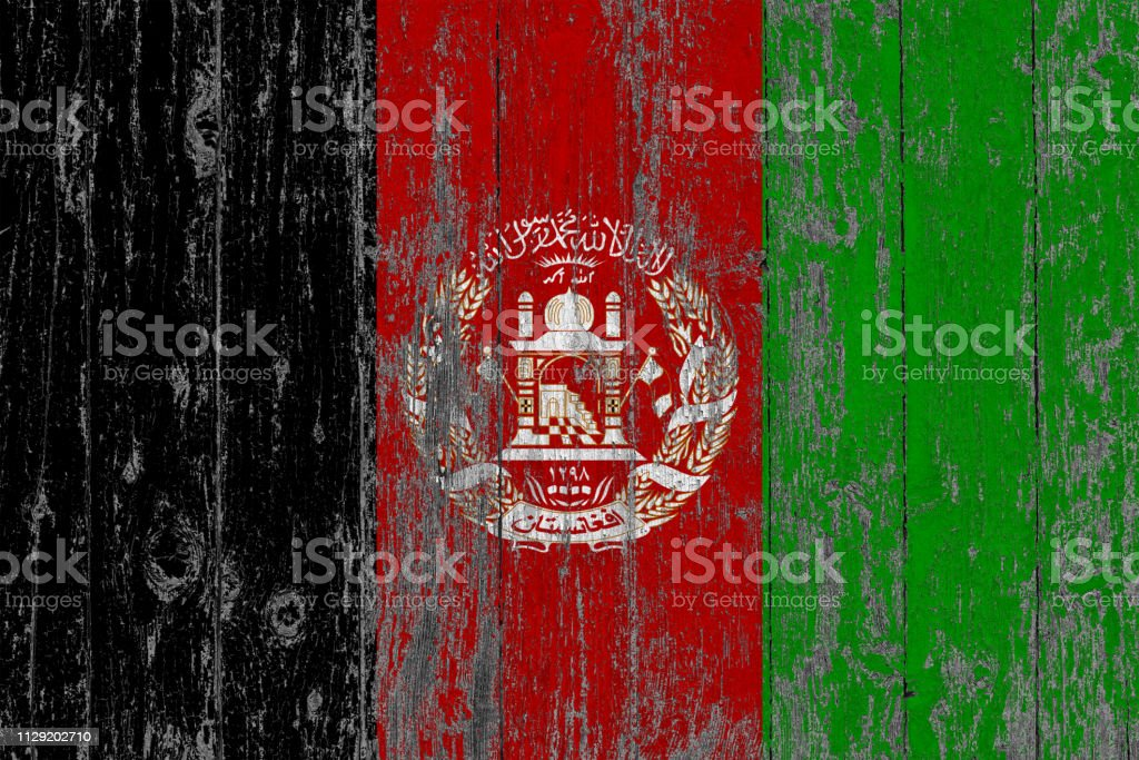 Flag of Afghanistan painted on worn out wooden texture background. stock photo