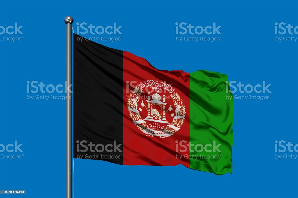 Flag of Afghanistan waving in the wind against deep blue sky. stock photo