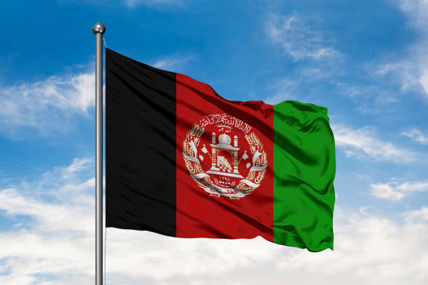 Flag of Afghanistan waving in the wind against white cloudy blue sky. stock photo