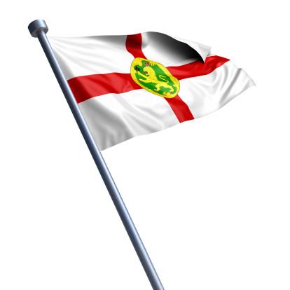 Flag of Alderney on modern metal flagpole.