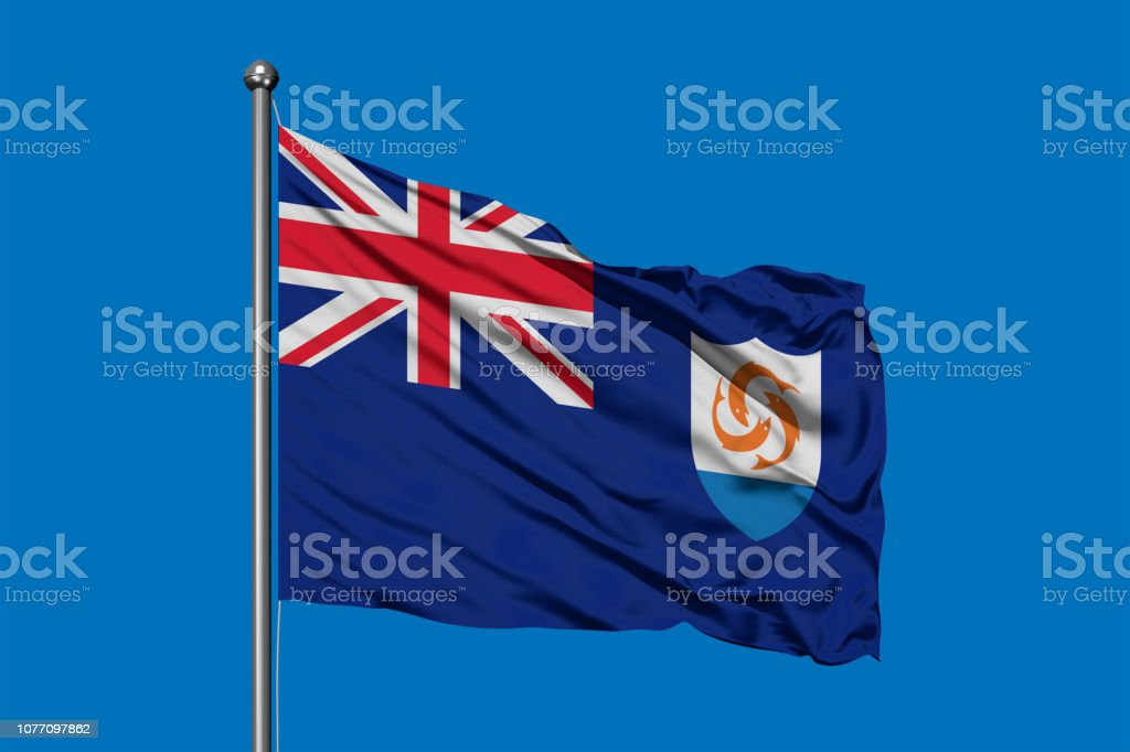 Flag of Anguilla waving in the wind against deep blue sky. stock photo