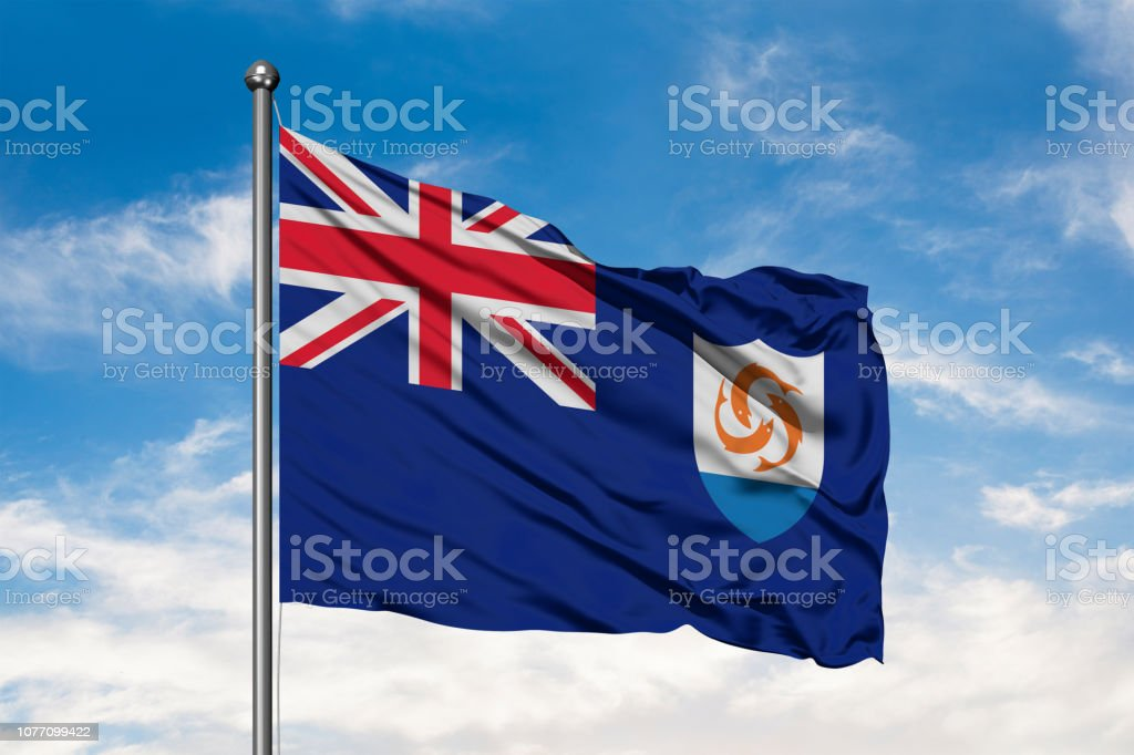 Flag of Anguilla waving in the wind against white cloudy blue sky. stock photo