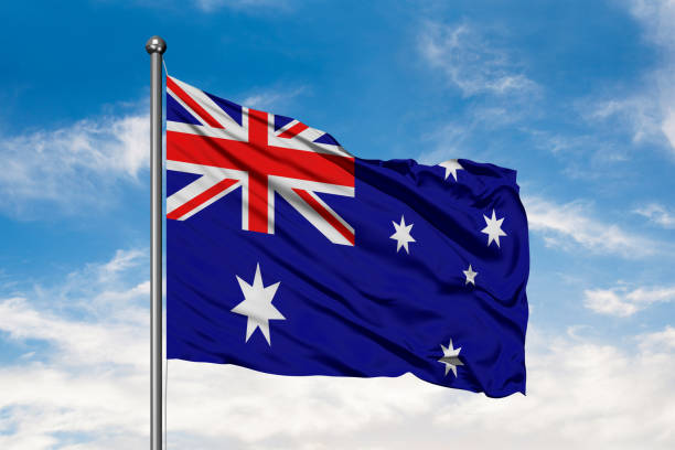 Flag of Australia waving in the wind against white cloudy blue sky. Australian flag. stock photo