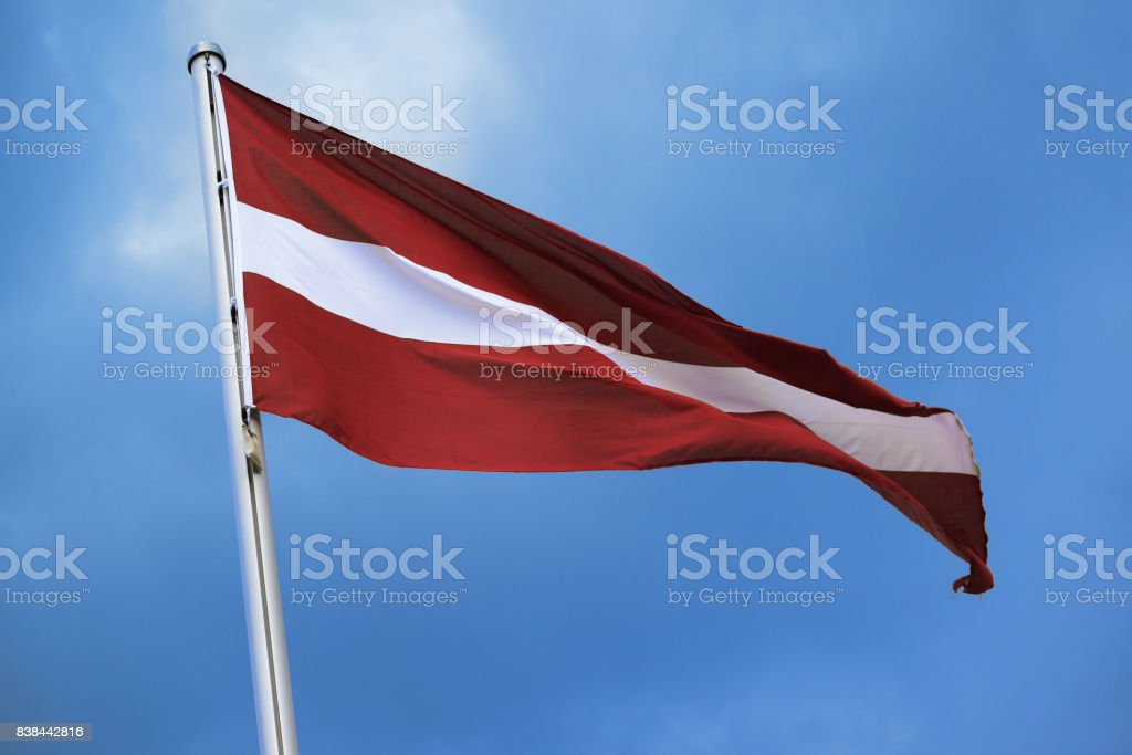 Flag of Austria, with stripes in red, white, red, national symbol or sign of the european country, fluttering in the wind against the blue sky with clouds on a sunny day stock photo