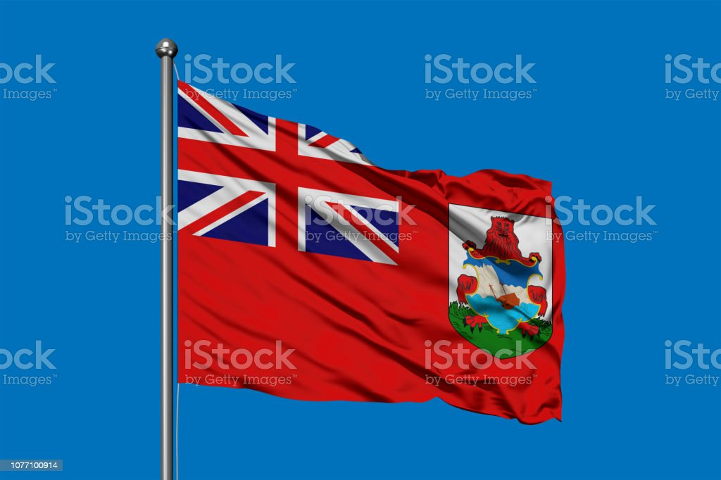 Flag of Bermuda waving in the wind against deep blue sky. stock photo