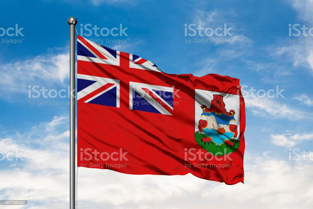 Flag of Bermuda waving in the wind against white cloudy blue sky. stock photo