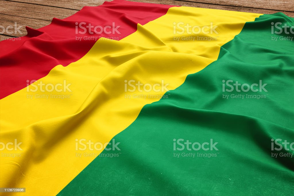 Flag of Bolivia on a wooden desk background. Silk Bolivian flag top view. stock photo