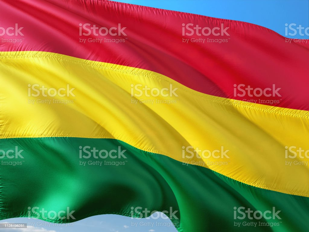 Flag of Bolivia waving in the wind against deep blue sky. High quality fabric. stock photo
