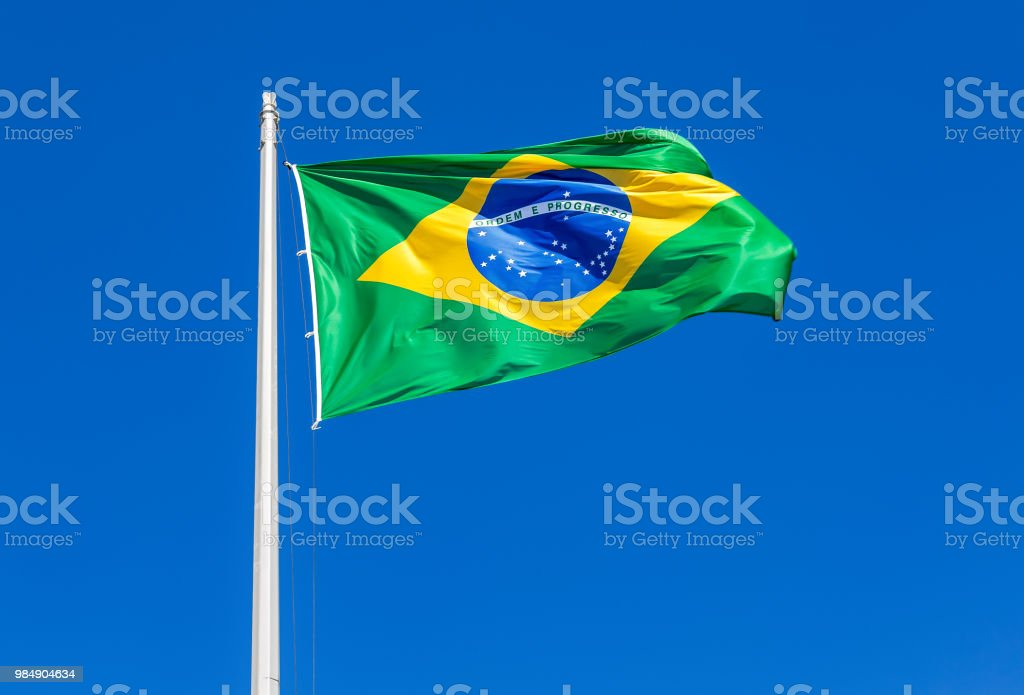 Flag of Brazil waving in the wind against the sky stock photo