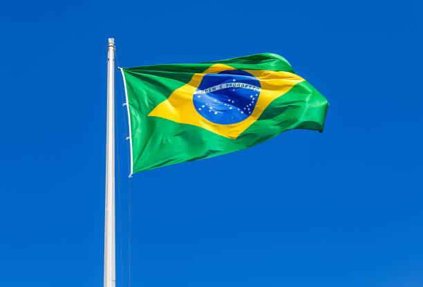 flagge von brasilien winken in den wind gegen den himmel - brasilien stock-fotos und bilder