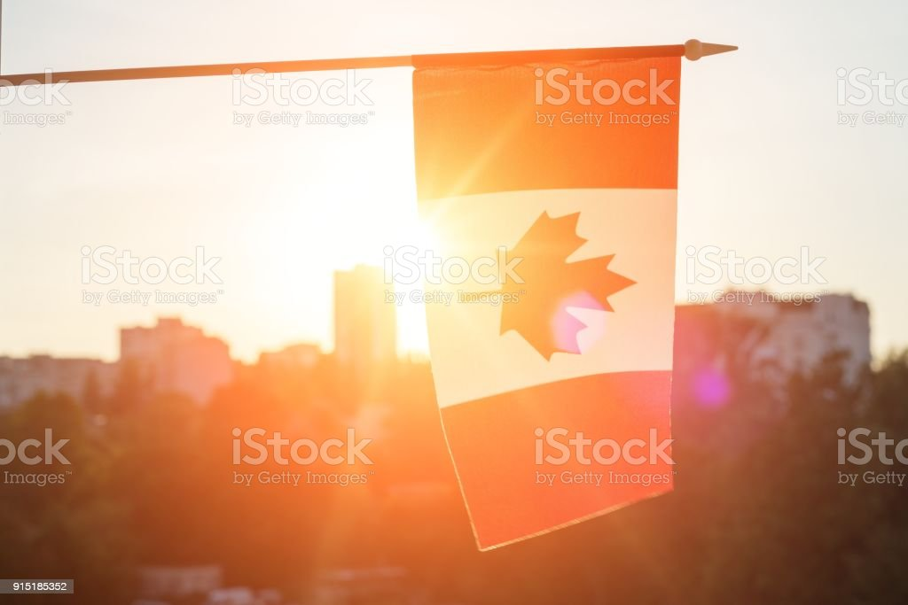 Flag of Canada from window sunset background stock photo