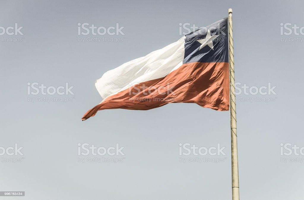 Bandeira do Chile voa em um vento forte contra um céu azul brilhante com o brilho do sol - foto de acervo