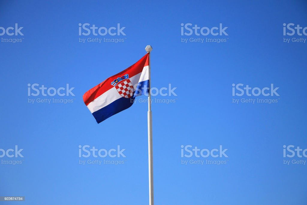 Flag of Croatia with flag pole waving in the wind with blue sky in background - foto stock