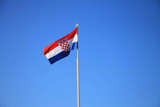 Bandeira da Croácia com mastro balançando ao vento, com céu azul em fundo - foto de acervo