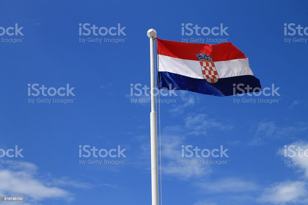 Flag of Croatia with flag pole with blue sky in background stock photo
