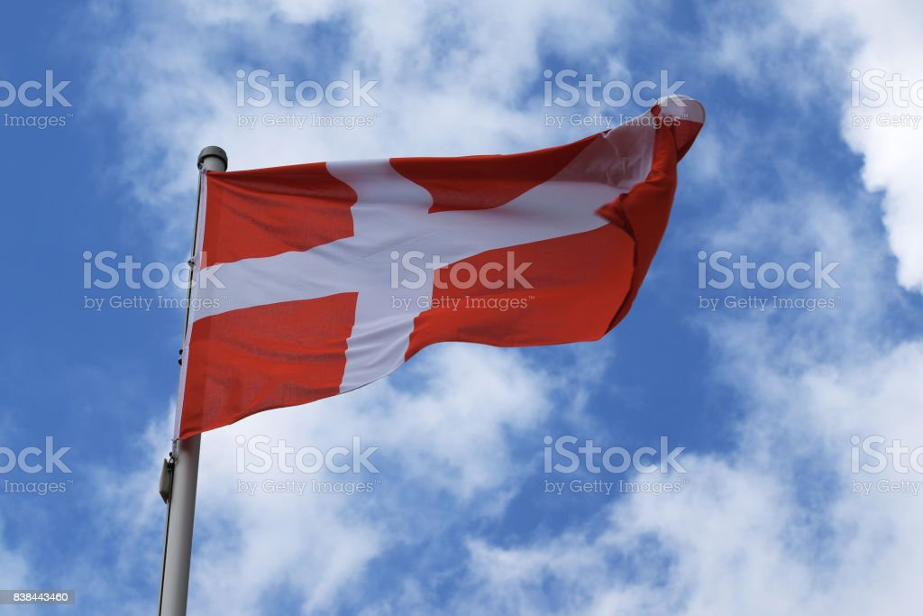 Flag of Denmark with a white cross on a red background, national symbol or sign of the european country, fluttering in the wind against the blue sky with clouds on a sunny day stock photo