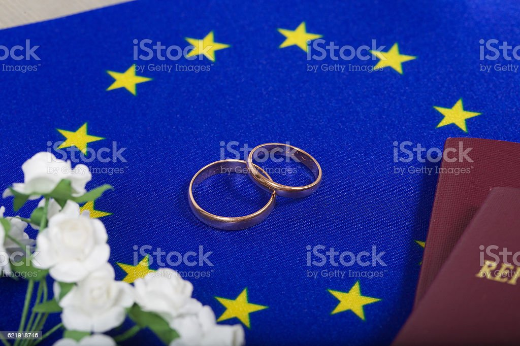 Flag of EU ,two marriage rings,passes. Top view stock photo