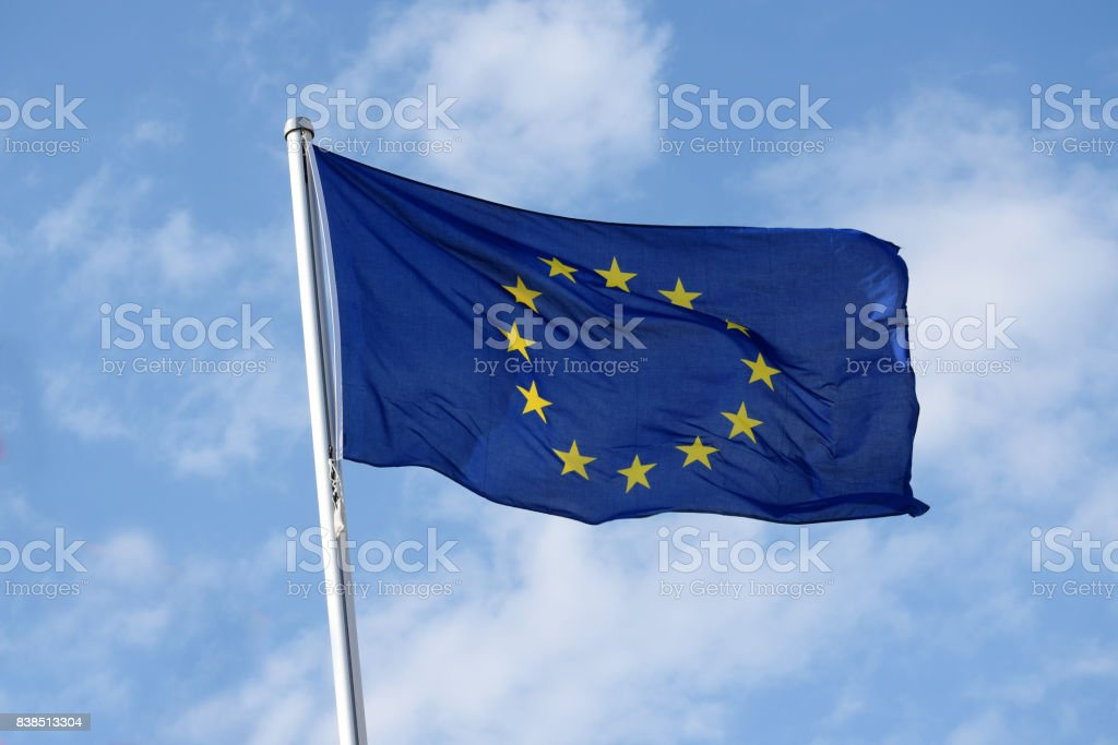 Flag of europe with yellow stars on a blue background as a symbol of the associated countries, fluttering in the wind against the blue sky with clouds on a sunny day stock photo