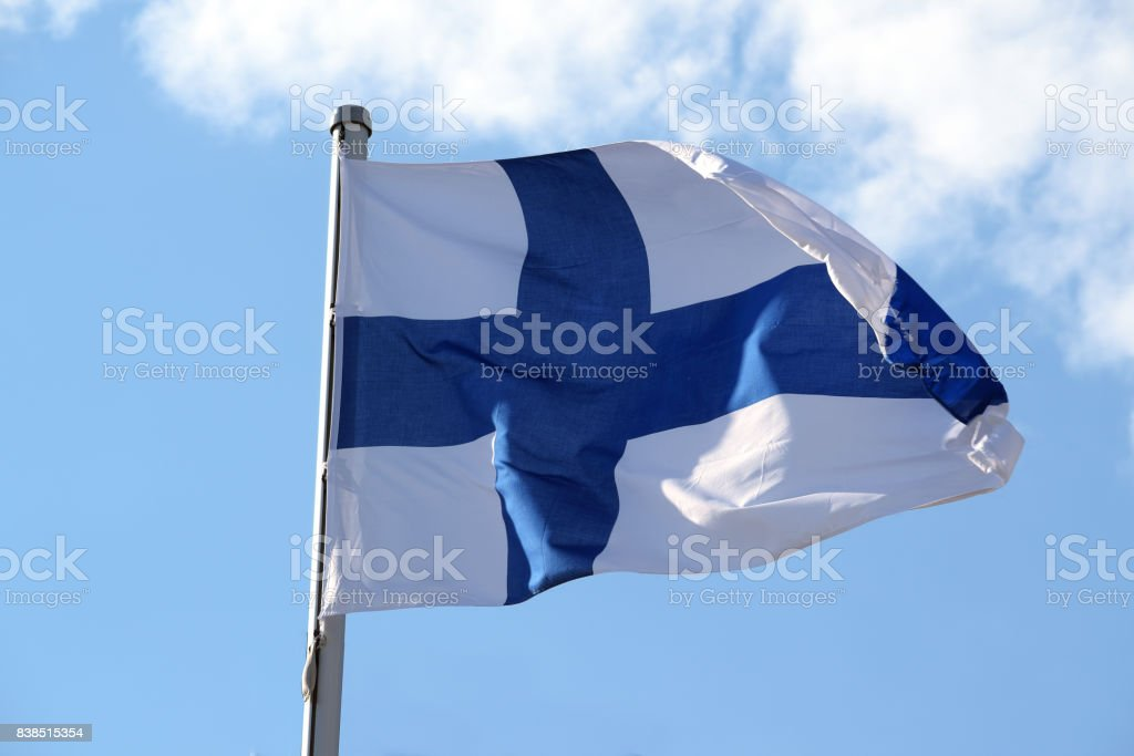 Flag of Finland with a blue cross on a white background fluttering against the blue sky, symbol or sign of the Finnish state belonging to europe stock photo