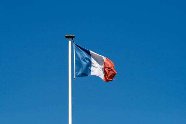 Flag of France floating at the top of a mast stock photo