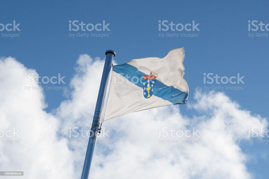 Flag of Galicia waving on the sky stock photo