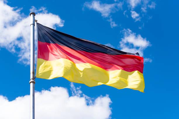 flagge von deutschland gegen blauen himmel in berlin - stoffe berlin stock-fotos und bilder