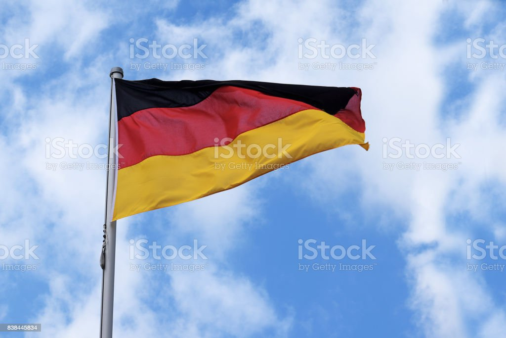 Flag of Germany with stripes in red, black and gold, national symbol or sign of the european country, fluttering in the wind against the blue sky with clouds on a sunny day stock photo