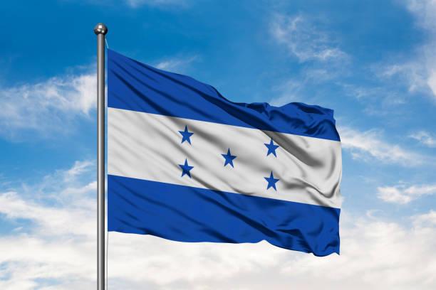 bandera de honduras ondeando en el viento contra un cielo azul nublado blanco. bandera de honduras. - bandera de honduras fotografías e imágenes de stock