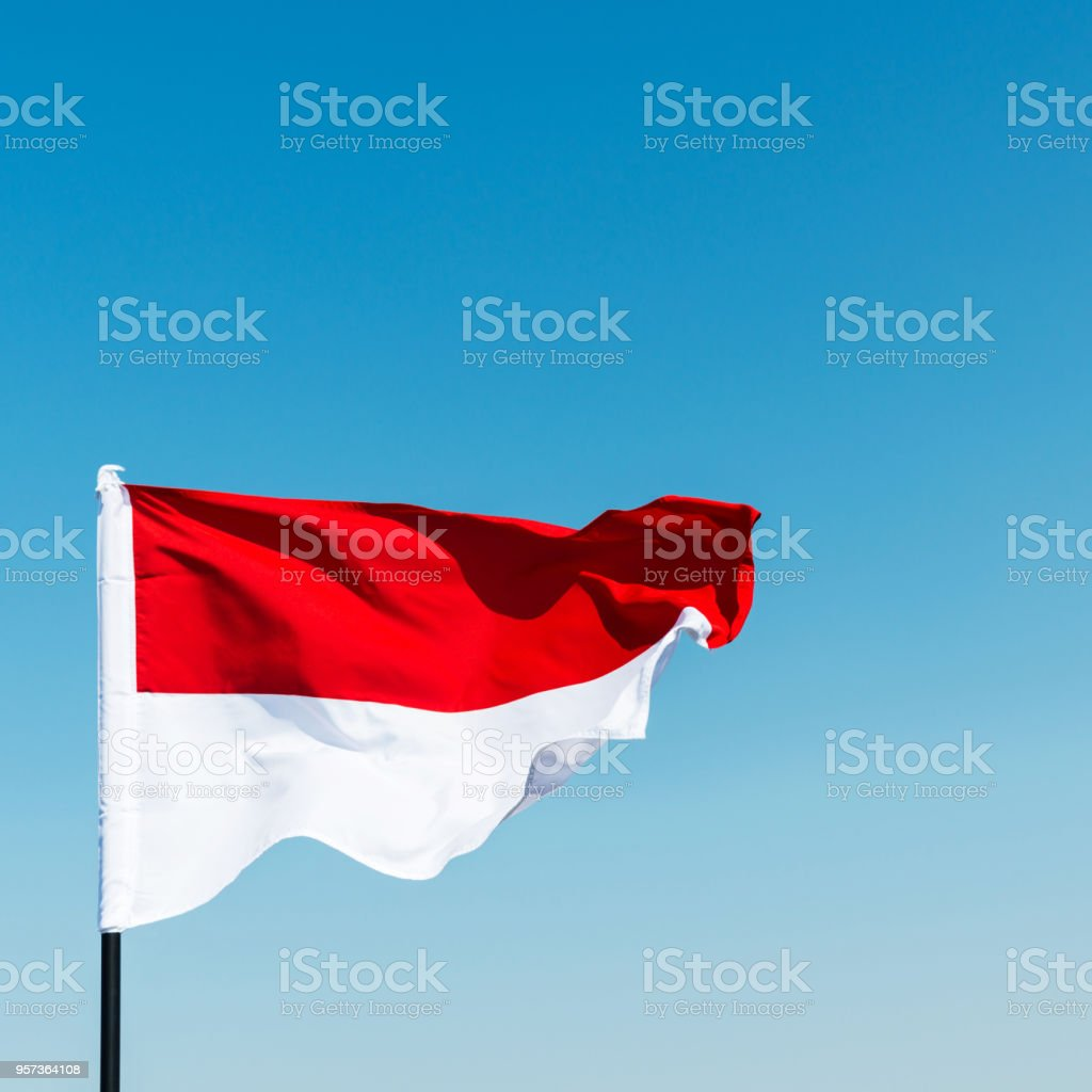 Flag of Indonesia against blue sky stock photo