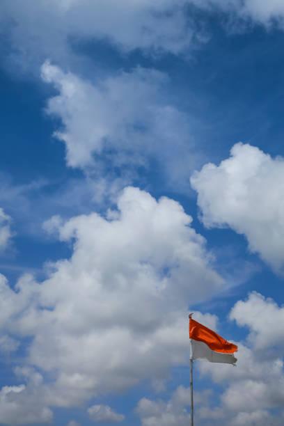 bandeira da indonésia contra o céu azul nublado - bandeira da indonesia - fotografias e filmes do acervo