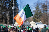 Flag of Ireland close-up in hands on background of blue sky during the celebration of St. Patrick's Day in the city