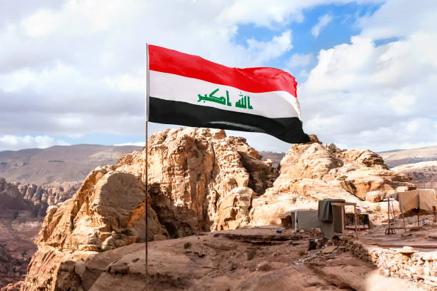 Flag of Islamic republic of Iraq waving in mountain background, cloudy skies stock photo