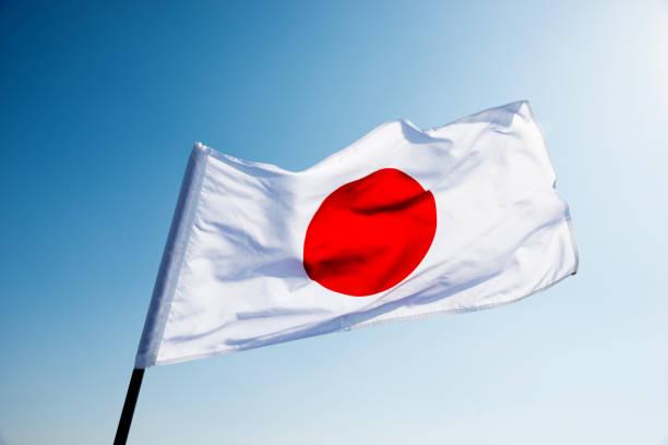Bandera de Japón en el viento saludar con la mano - foto de stock