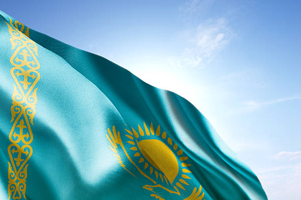 Flag of Kazakhstan waving in the wind Flag of Kazakhstan waving in the wind. Blue sunny sky in the background. Horizontal orientation. kazakhstan stock pictures, royalty-free photos & images