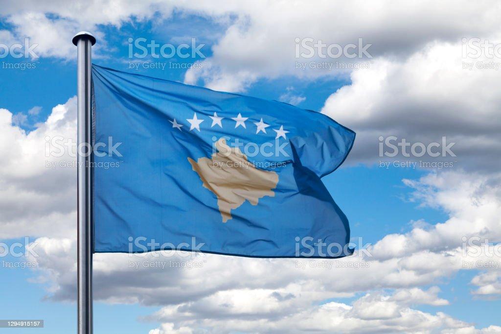 Flag of Kosovo Close-up on the flag of Kosovo waving atop of its pole. Balkans Stock Photo