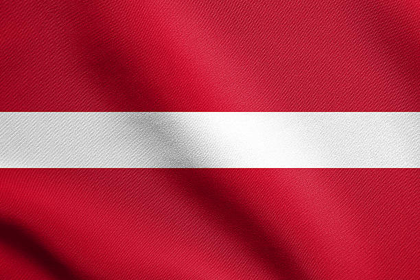 Flag of Latvia waving in wind with fabric texture stock photo