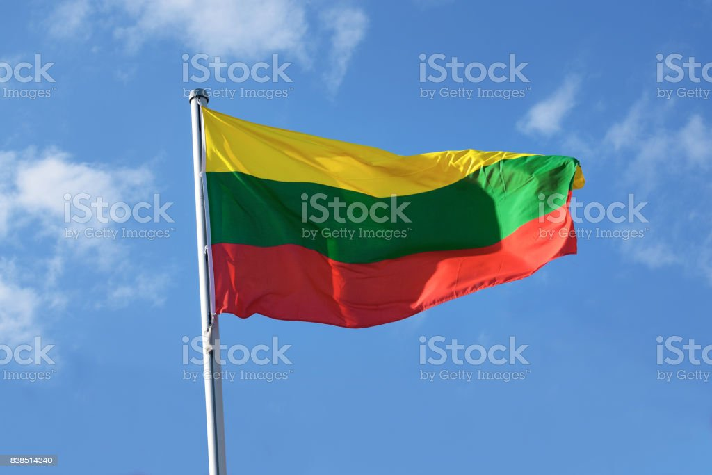 Flag of Lithuania with horizontal stripes in yellow, green and red, national symbol or sign of european country, fluttering in the wind against the blue sky with clouds on a sunny day stock photo