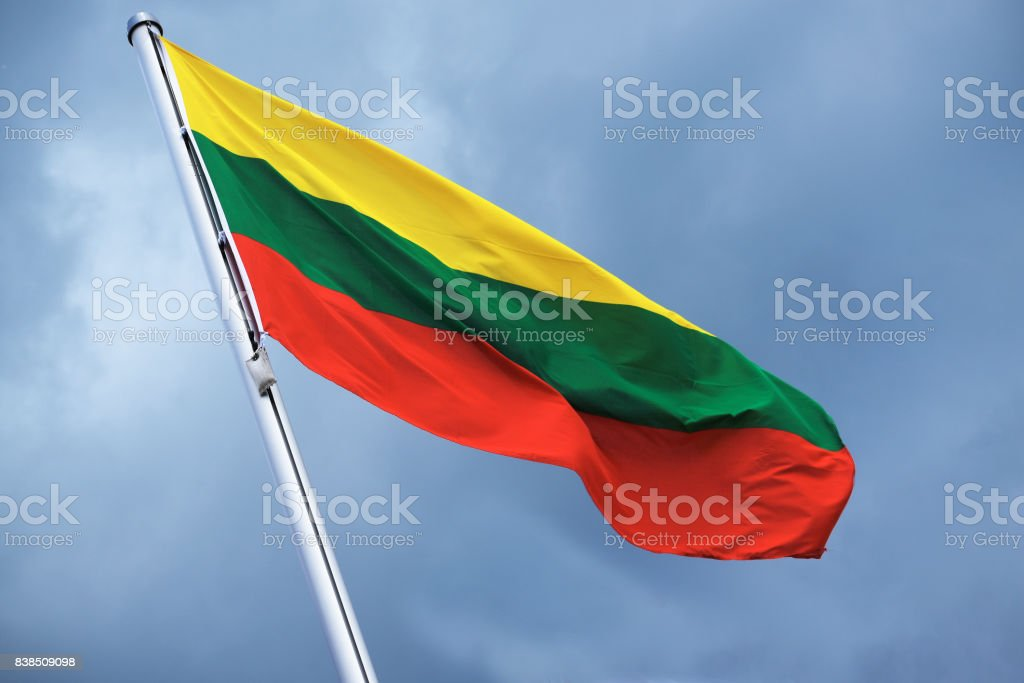 Flag of Lithuania with stripes in yellow, green and red, national symbol or sign of the country, fluttering in the wind against the cloudy sky on a sunny day stock photo