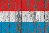 Flag of Luxembourg painted on worn out wooden texture background.
