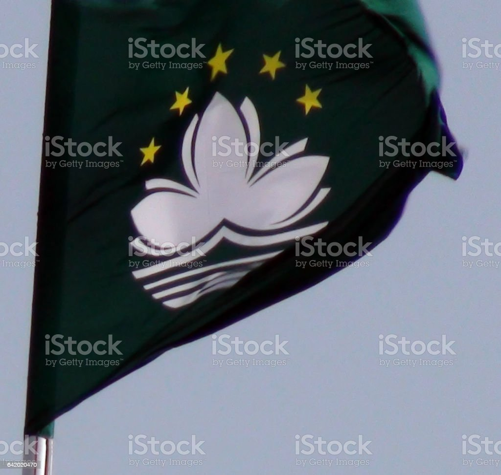 Flag Of Macau Waving Against Blue Sky In Macau stock photo