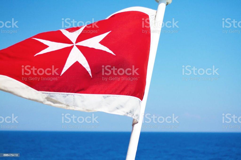 Flag of Malta Flies Against Vibrant Blue Sea/Sky stock photo